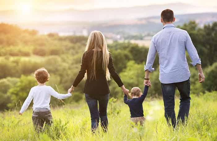 Family walking in green field